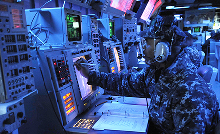 YOKOSUKA, Japan (Feb. 14, 2012) Operations Specialist 1st Class Lionel Mahoney, training supervisor aboard the Arleigh Burke-class guided-missile destroyer USS Stethem (DDG 63), records enemy locations during a fleet synthetic training scenario.